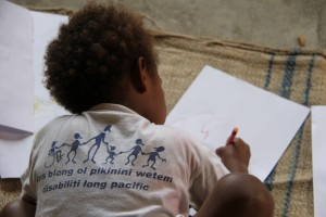 Boy from Vanuatu wearing project t-shirt and drawing a picture