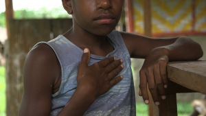 Young girl from Vanuatu leaning on a railing looking at the camera with her hand resting on her chest over her heart