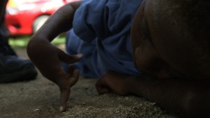 A young boy from Vanuatu lies on his side drawing in the sand with his finger