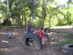 Pikinini (children) playing on play equipment made out of tractor tyres