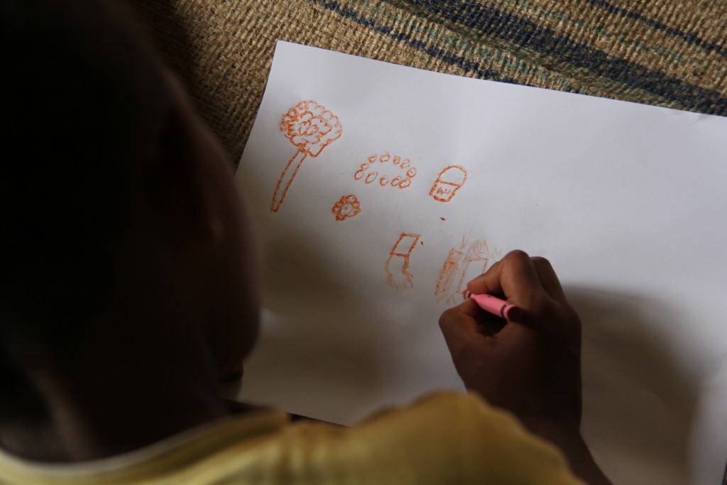 A photo taken looking over the shoulder of a child lying on a mat drawing a picture