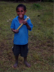 A small boy holding a stick and laughing