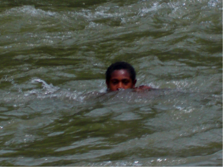 A boy swimming in a fast-rushing river