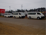 Three white minibuses lined up at a bus stop