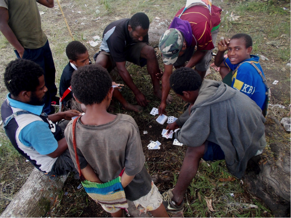 A group of people, adults and children, playing a card game on the ground