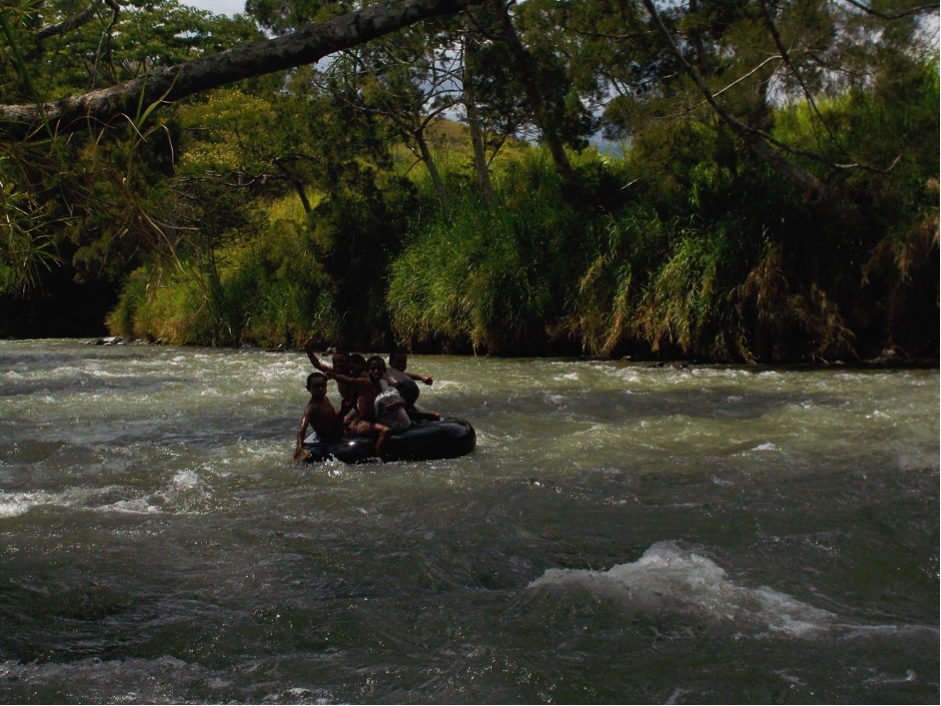 A group of children floating on a tyre tube down a rushing river