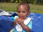 A small child sitting on a tarpaulin wearing a bib and eating a piece of fruit