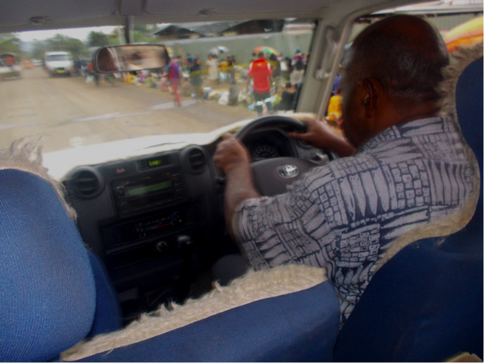 The view of a man driving a vehicle, taken from the back seat looking out onto the road ahead
