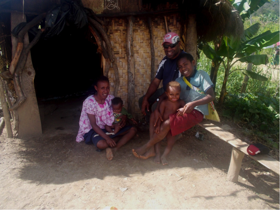 A family of mother, father and three children pose in front of a house