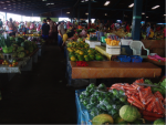 A undercover market with stalls selling fresh fruit and vegetables