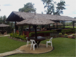 The grounds of a hotel, with lawns, tables and chairs under umbrellas and a large thatch-roofed outdoor eating area
