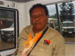 A village magistrate wearing a khaki-coloured shirt with a PNG flag badge on the picket