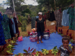 A woman stands in a market clothes stall with pots of food around her feet