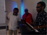 A group of three blind or vision impaired musicians. One is playing a keyboard