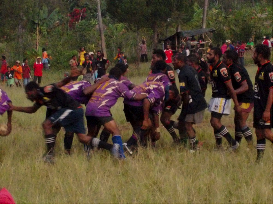 Two rugby league teams - one in purple and one team in black - playing a game