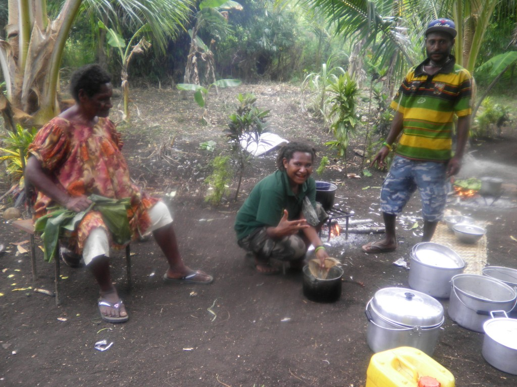 A young girl washing a cooking pot while a lady and a man watch on