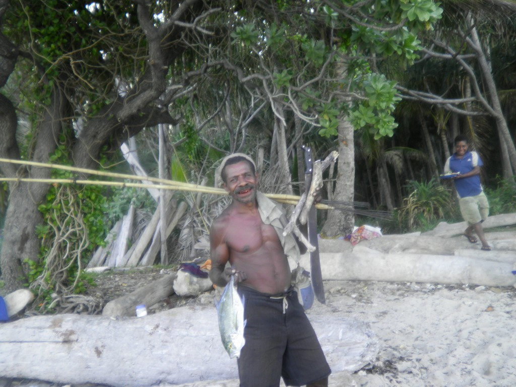 A fisherman holding a fish in one hand, and two spears and a large knife in the other