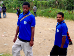 Two school boys wearing royal blue school shirts pose for the camera