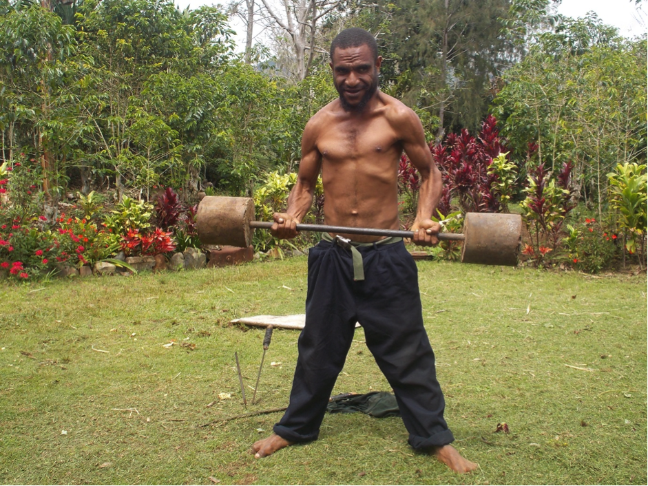 A man standing in a garden lifting home-made barbells